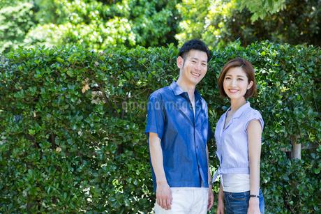 緑の前で微笑む20代30代カップルの写真素材 [FYI01734412]
