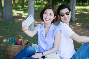 緑の中ピクニックをする20代30代カップルの写真素材 [FYI01734437]