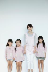 微笑む3人の園児と保育士の写真素材 [FYI01734447]