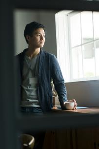 窓際に立つ30代男性の写真素材 [FYI01734491]