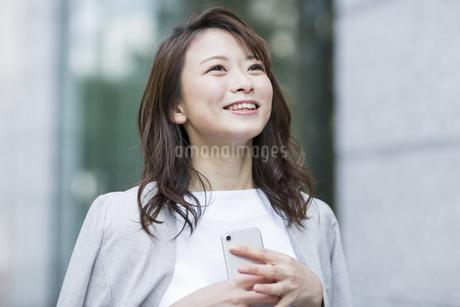 スマートフォンを持ち笑顔のビジネスウーマンの写真素材 [FYI01734504]