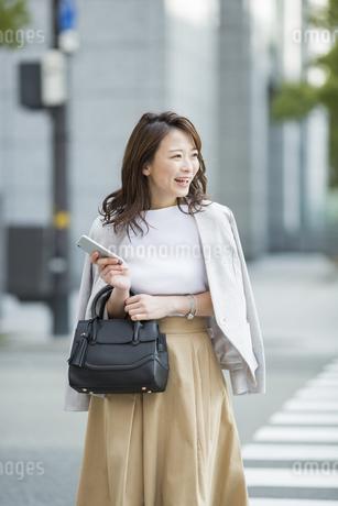 横断歩道を歩くビジネスウーマンの写真素材 [FYI01734524]