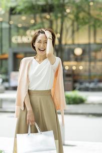 ショッピングバッグを持って微笑む女性の写真素材 [FYI01734525]