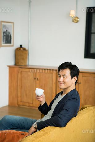 ソファに座る笑顔の30代男性の写真素材 [FYI01734614]