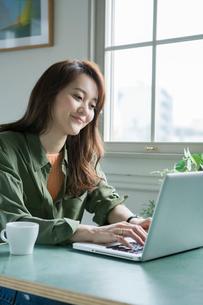 室内でパソコンを操作する30代女性の写真素材 [FYI01734629]