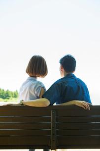 ベンチに座る20代30代カップルの後ろ姿の写真素材 [FYI01734632]
