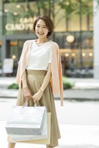 ショッピングバッグを持って微笑む女性の写真素材 [FYI01734648]