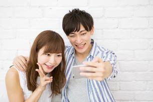 自撮りをする笑顔の20代カップルの写真素材 [FYI01734682]