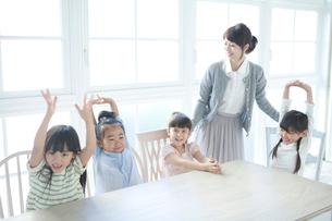テーブルを囲む4人の園児の写真素材 [FYI01734693]