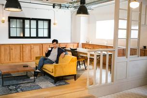 ソファに座り飲み物を飲む30代男性の写真素材 [FYI01734698]