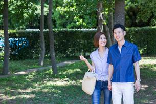 公園を散歩する20代30代カップルの写真素材 [FYI01734734]