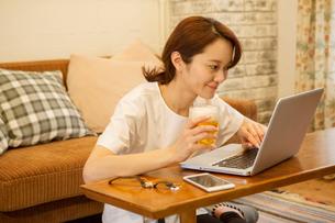 パソコンを操作しながらビールを飲む30代女性の写真素材 [FYI01734748]