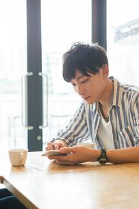 スマホを操作する20代男性の写真素材 [FYI01734781]