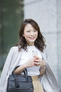 スマートフォンを持ち笑顔のビジネスウーマンの写真素材 [FYI01734799]