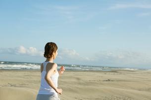 浜辺でランニングをする20代女性の写真素材 [FYI01734826]