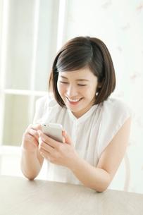座りながら携帯を操作する20代女性の写真素材 [FYI01734851]