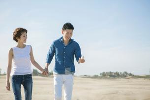 砂浜を歩く20代30代カップルの写真素材 [FYI01734859]