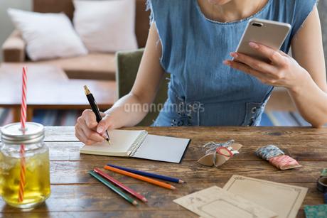 スマホを持ちメモをとる女性の手元の写真素材 [FYI01734866]
