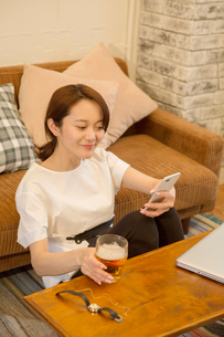 スマホを見ながらビールを飲む30代女性の写真素材 [FYI01734889]