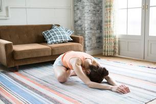 部屋でストレッチをする30代女性の写真素材 [FYI01734890]