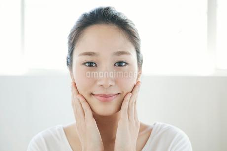 頬をなでる20代女性の写真素材 [FYI01734897]