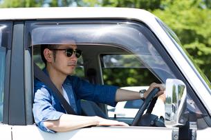 サングラスをかけて運転する30代男性の写真素材 [FYI01734907]