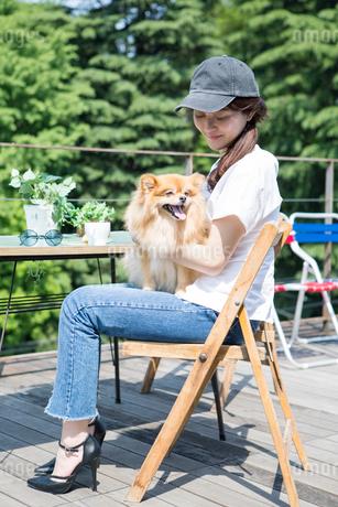 屋外のカフェで飼い犬を抱きかかえる女性の写真素材 [FYI01734912]