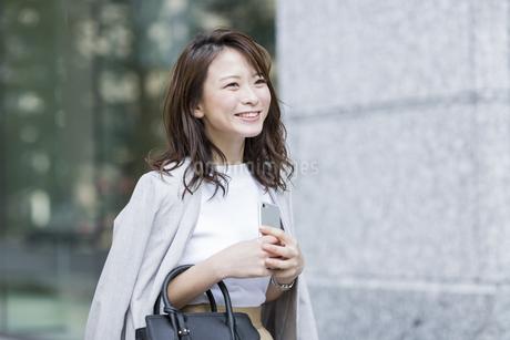 スマートフォンを持ち笑顔のビジネスウーマンの写真素材 [FYI01734960]