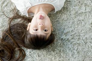 寝転び舌を出す女の子の写真素材 [FYI01734968]