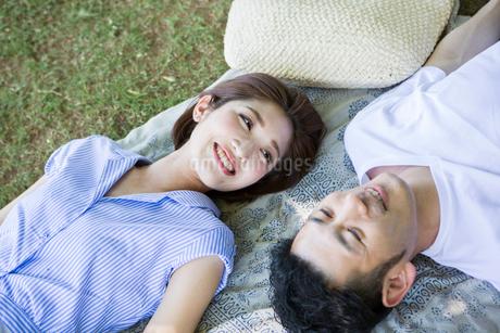 寝転んで向き合う20代30代カップルの写真素材 [FYI01735011]