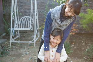 庭先で微笑む母と娘の写真素材 [FYI01735046]