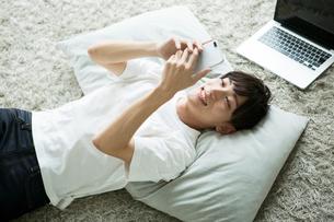 部屋で寝転がりながらスマホを操作する20代男性の写真素材 [FYI01735063]