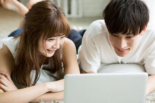 パソコンを見る20代男女の写真素材 [FYI01735070]