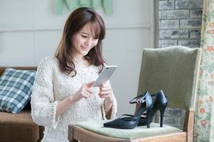 靴の写メを撮る笑顔の女性の写真素材 [FYI01735076]