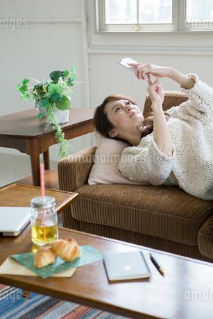 ソファに寝転がりスマホを操作する30代女性の写真素材 [FYI01735097]