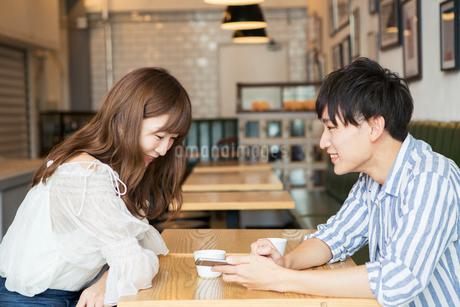 カフェでくつろぐ20代男女の写真素材 [FYI01735112]