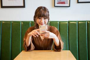 スマホを操作する笑顔の20代女性の写真素材 [FYI01735117]