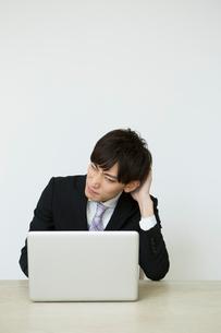 パソコンを操作するスーツ姿の20代男性の写真素材 [FYI01735148]