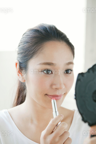 口紅を塗る20代女性の写真素材 [FYI01735178]