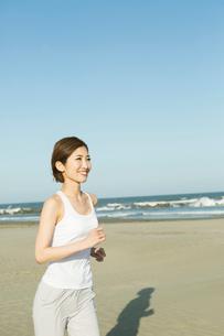 浜辺でランニングをする20代女性の写真素材 [FYI01735183]