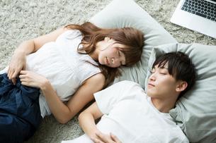 部屋で昼寝をする20代男女の写真素材 [FYI01735187]