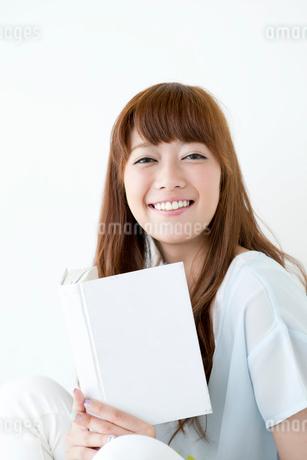 本を持つ笑顔の女性の写真素材 [FYI01735195]