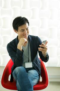椅子に座りスマホを見る笑顔の30代男性の写真素材 [FYI01735198]