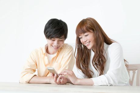 一緒に携帯電話を見る20代カップルの写真素材 [FYI01735210]