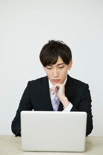 パソコンを操作するスーツ姿の20代男性の写真素材 [FYI01735225]