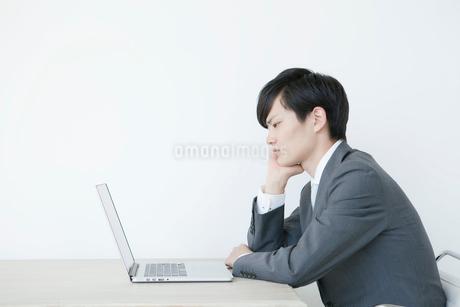 肘をつきながらノートパソコンを見るヤングビジネスマンの写真素材 [FYI01735230]