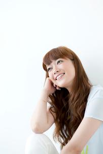 肘をつく笑顔の若い女性の写真素材 [FYI01735244]