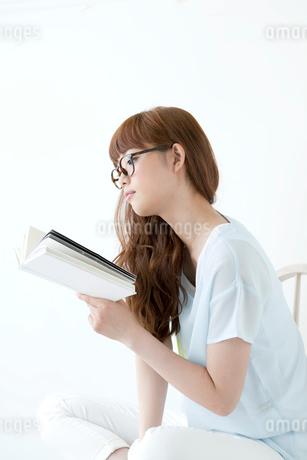 椅子に座り読書をする若い女性の写真素材 [FYI01735246]