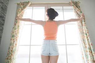 部屋のカーテンを開ける女性の写真素材 [FYI01735252]
