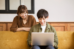 ソファに座りパソコンを見る笑顔の20代男女の写真素材 [FYI01735256]